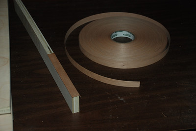 A closeup of a test board with a small piece of edge banding. The banding is cherry, the plywood is Birch. This roll contains 250 feet of cherry wood.