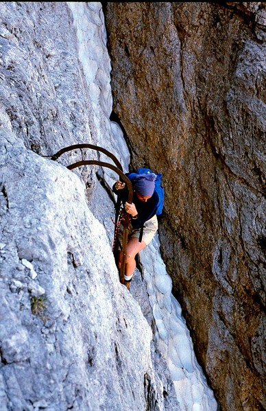 Judy navigates one of the long iron ladders on the via ferrata that allows hikers to climb rockface walls in the Dolomites, 1986.