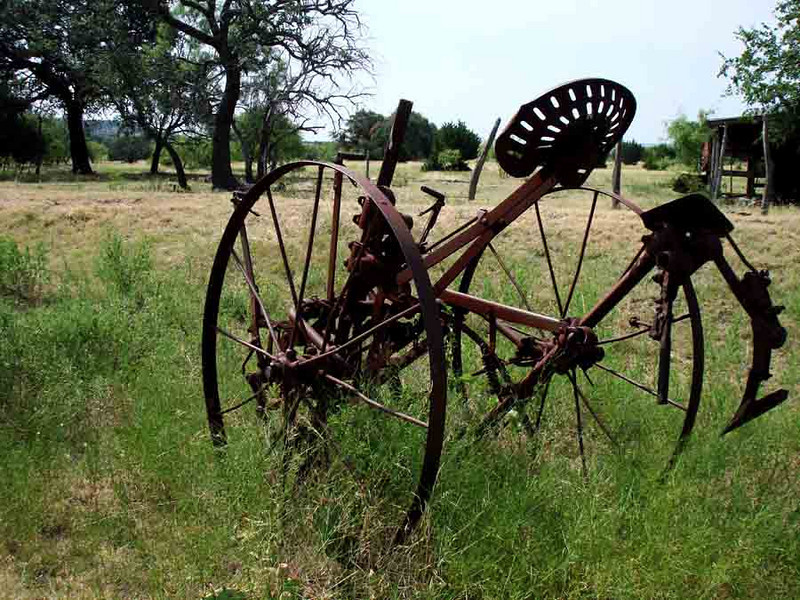 FARM EQUIPMENT<br /> I'm not too up on my farm machinery, but from the looks of the blade on the right, I'd say this was a horse-drawn riding plow.