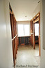 View down upstairs hallway showing framing of bathroom wall with sheet rock removed.  Door way on right is original entrance to master bath.