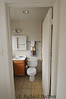 Looking in original master bathroom with single sink, wc and tub to the right of door