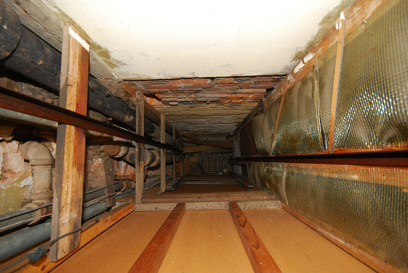 Looking down the dumbwaiter shaft to the basement floor.  One of the ropes (lower left of the frame) ends nearby; the other extends all the way down.