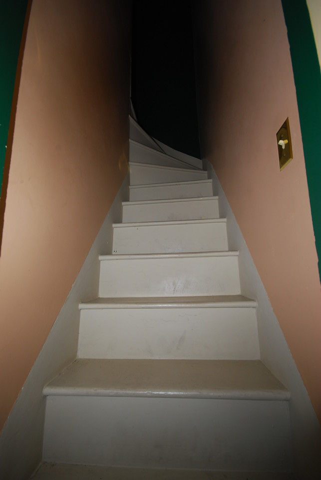 This narrow, steep, rail-less stairway leads from the kitchen to the maid's hallway.