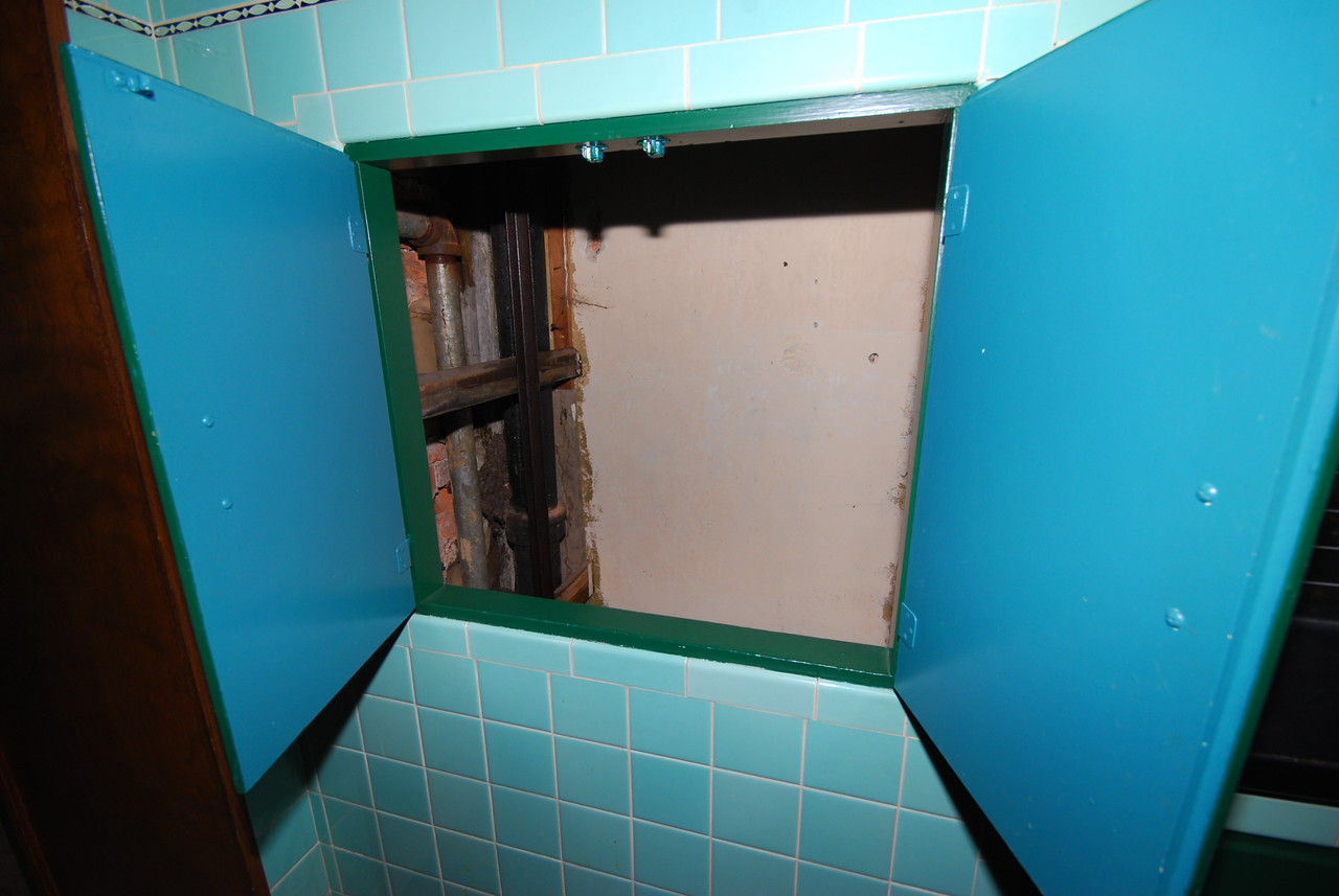 This is the dumbwaiter door in the kitchen. Since the carriage is on the second floor, we're looking into the shaft here.