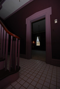The foyer. Through the lavender door frame is the TV room.