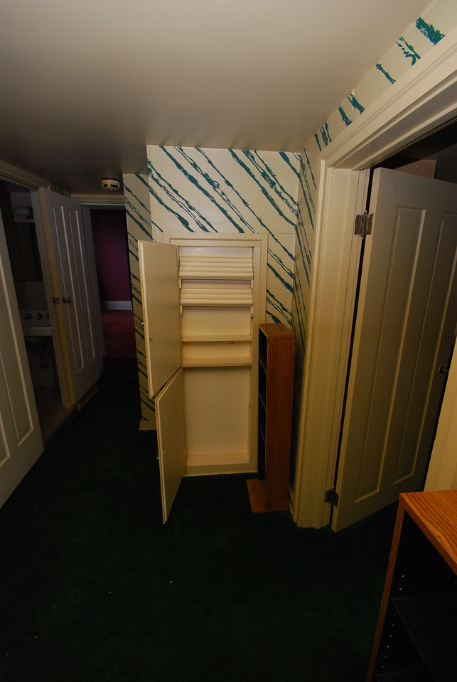 The built-in ahead would be used for storing sewing supplies. Thread holders are at top. The door at right leads to the maid's quarters. The red bedroom is visible ahead.