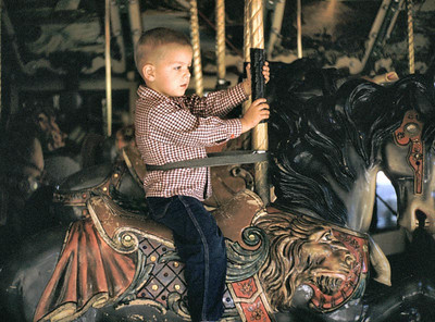 Gary riding on carousel in Griffith park near Glendale Calif.