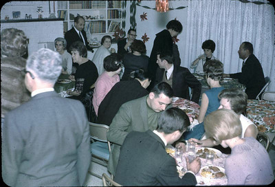 Church social, a progressive dinner at the Braun house. Names in this photo (thanks to Dorothy Braun): Helen Vanderkolk is sitting between Howard and Kenny Kauffman. The lady in front of Kenny is Audrey Johnson. Howard and Becky Lee are at the next table. Becky is in the blue dress. The man at the front table in the green suit is Roger Ley and the woman next to him is his wife Pat. The man in the foreground with the white hair looks like Warren Ross, but I am not certain.