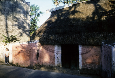 In front of a thatched roof hut in the Yucatan