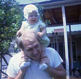 Jay is riding Kim on his shoulders in our backyard.
