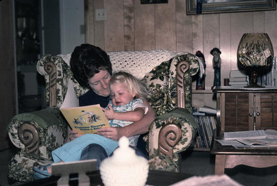 Grandma reading story to kim but it looks like she is reading it to her Grandma instead.