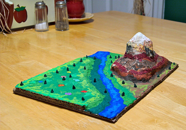 Landscape by Abigail and Mom, October 2005.   On the left, you can see a second layer of cardboard that raises the plain a little above the river.  Non-drying, pre-colored clay was applied on top.