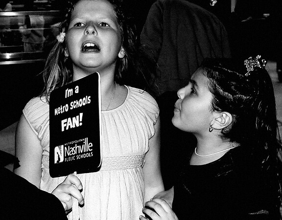 Abigail, age 9.    Doing something...  ...looks like a demonstration.   ...hmm, looks like her friend is trying to calm her down.   Or blow on her.    Ahh, that's it: it's a FAN! Abby is dying from the heat!  Duh!  ...and here I went for the hollywood starlet drama queen look, and lost all the color in her cheeks.  (Taken with the 2MP Olympus 2100 UZ)