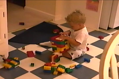 July 2000 Nicholas  is soo tried, playing with legos, points eyes & ears, eats yogurt with a straw & plays on steps with Tim