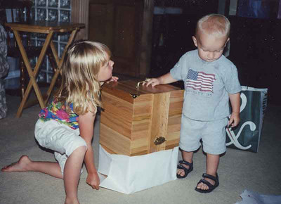 Jake was helping Paige open her doll chest that her grandpa edberg made for her Barbie dolls.