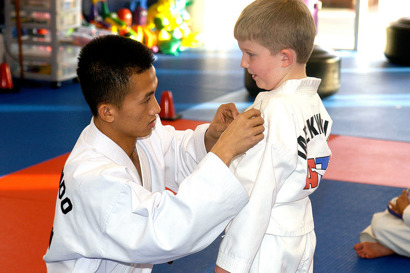 (12.21.2005)  Connor getting his new badge from Mr. Nguyen during his testing Taekwondo testing.