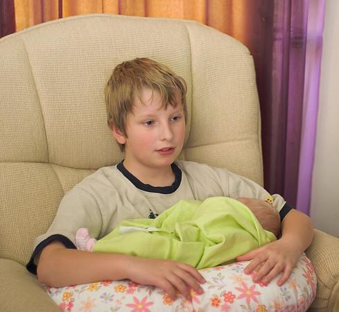 Joshua watching TV while holding Chloe.  2006-04-02 10:50
