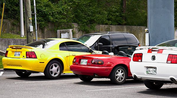 Tim's Red Miata between Ford Mustangs.