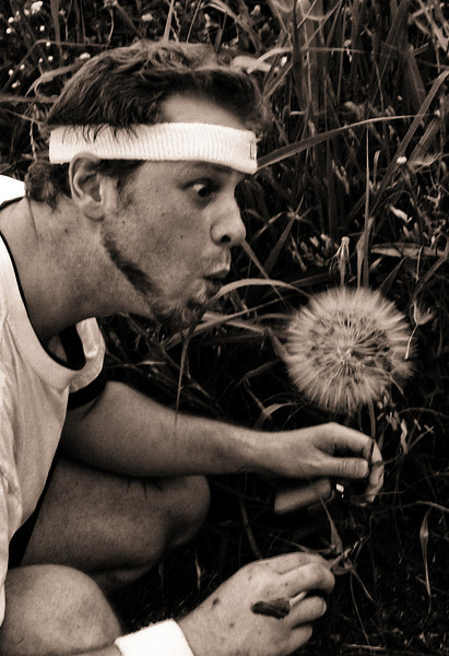 Tim pretending to blow the biggest dandelion.