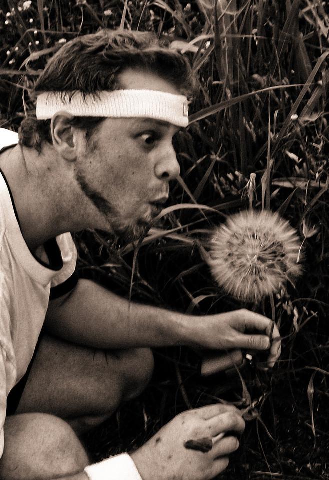 Tim pretending to blow the biggest dandelion.