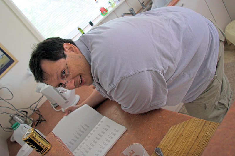 """Dennis helps in the kitchen - by reading the so called """"Adami Family History""""."""