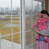 Olivia and Megan Gill look out the window from the kitchen at home in Hallsville, Missouri on January 28, 2006.