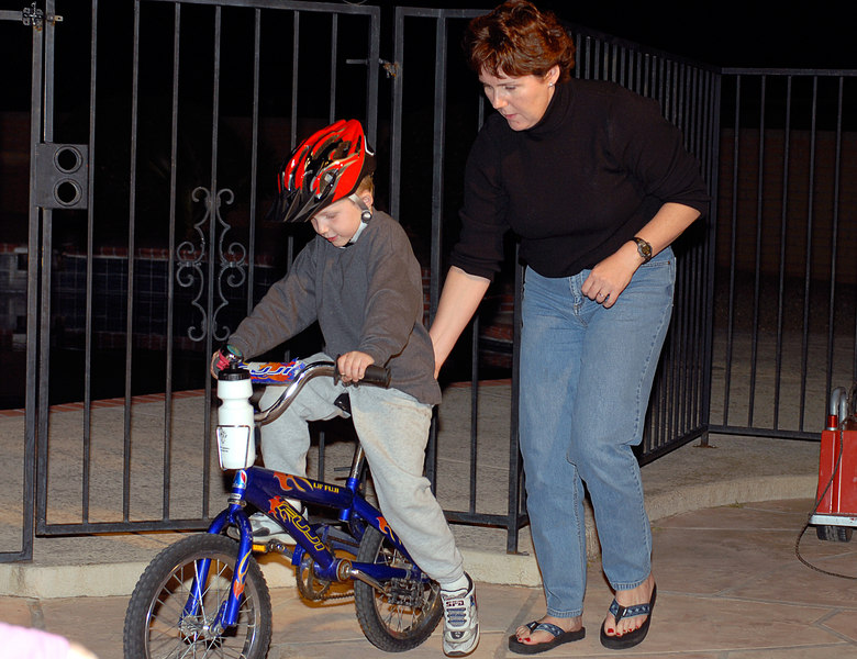(3.31.2006)  Mom teaching Connor how to ride his bike without training wheels.