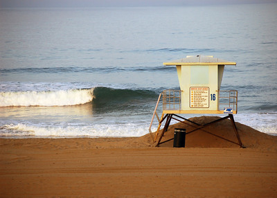 Lifeguard tower on overcast morning with wave breaking