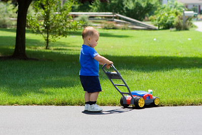 K.C. pushes his bubble mower up the driveway.