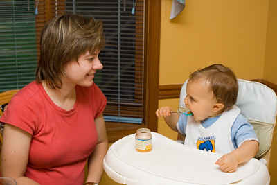 Mom coaches K.C. as he's shown interest in feeding himself with the spoon.