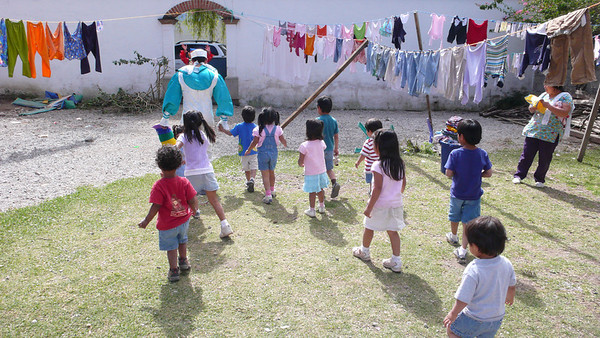 the clown leads the kids from the playground to the christmas fiesta