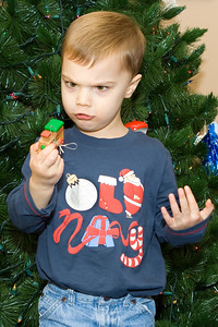 K.C. is supposed to be helping decorate the Christmas tree.  He is perplexed why the wheels don't turn on the train ornament.