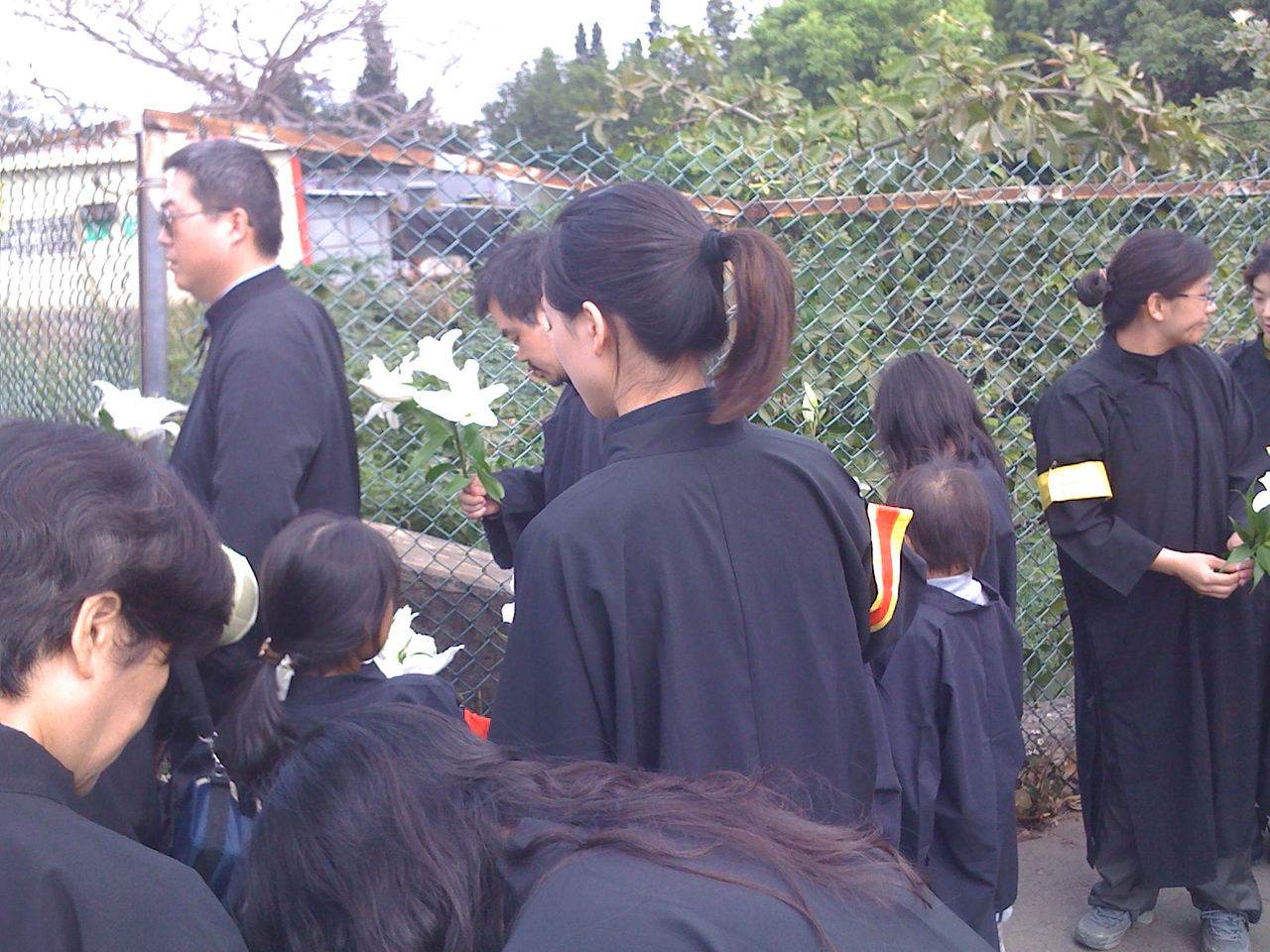 2008 11 26 Wed - Funeral family in black robes & colored armbands holding casablanca lillies