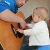helping papa to play a guitar