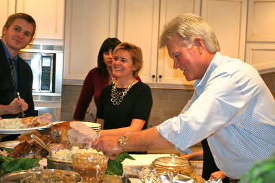 Host Mike serves the turkey with Chris, Debbie and Frazier looking on