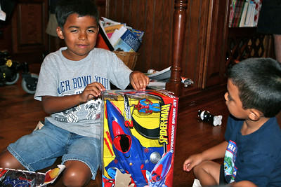 Big brother Jonathan helps Jesus open his toy