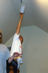 Collin uses his height to change a lightbulb