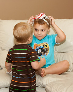 K.C. shows Ethan how to put the fabric coaster on his head.