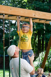 K.C. enjoys the monkey bars with help from Dad.