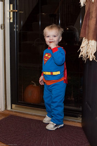 Super Ethan enjoys a lolipop while he waits for more trick or treaters.