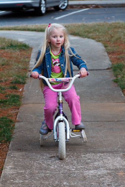Chloe riding a bicycle on the pathway i front of our apartment - December 2011