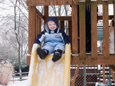 Ethan is ready for a ride down the slide regardless of the snow.