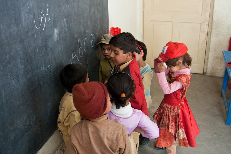 """One preschooler teaching the others the English alphabet. Because the school is short staffed, it was typical for the teachers to assign a student to teach other students. In this case the kids yelled out """"A, B"""" for about 20 minutes as the boy in red pointed back and forth at those two letters in turn."""