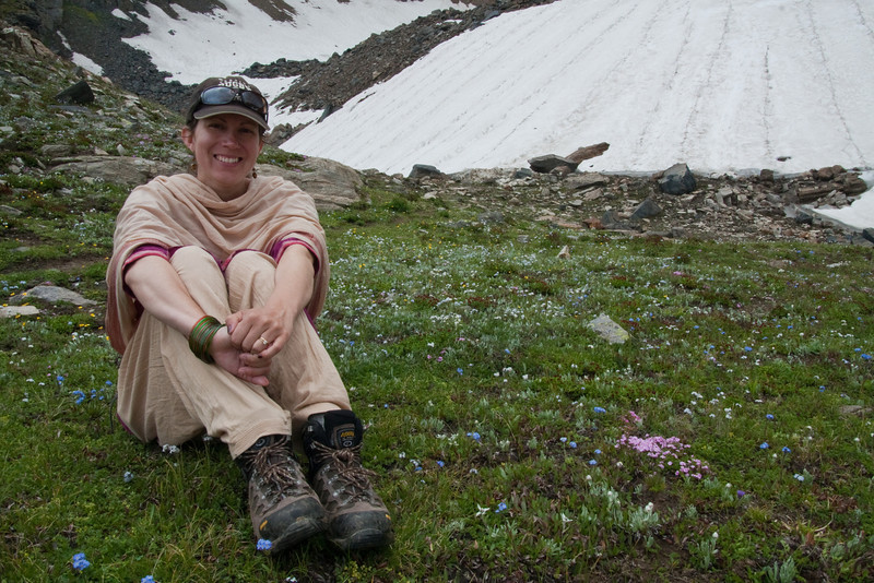 Erin resting amidst the wildflowers. We had to climb up the slick snowy slope in the background; our first major snow crossing. In the days ahead we would face much longer stretches over snow.