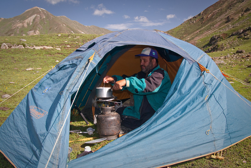 Basheer cooking breakfast in the vestibule of his tent. The horse carried the heavy gas cylinder and all our other stuff.
