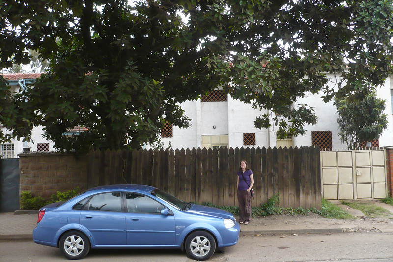 Erin with our blue rental car in front of the house. 2011.