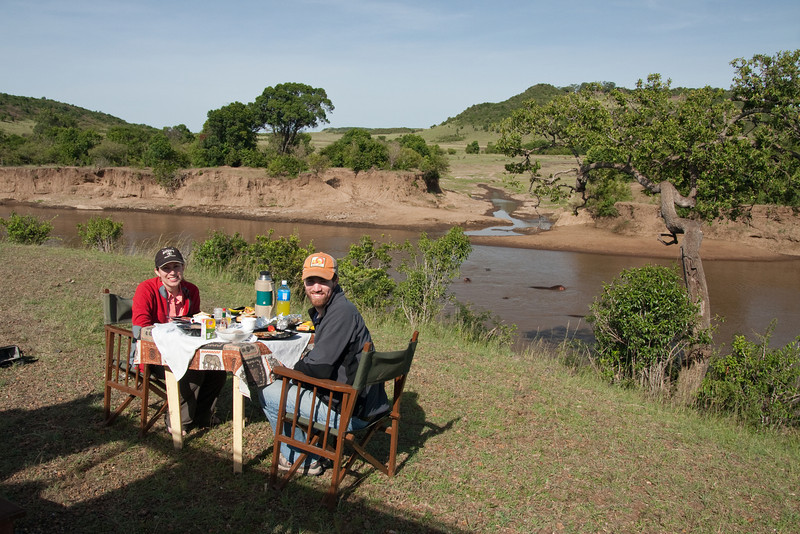 "On our last morning in Maasai Mara we were treated to a delicious ""bush breakfast"" on the shores of the Mara River.  You can see hippos frolicking in the muddy water."