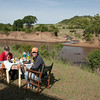 """On our last morning in Maasai Mara we were treated to a delicious """"bush breakfast"""" on the shores of the Mara River.  You can see hippos frolicking in the muddy water."""
