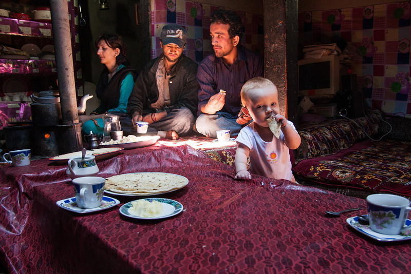 Sienna enjoying some traditional Wakhi roti inside Rehman's family's house. Rehman's family belongs to the Wakhi ethnic community, a tribe with their own language and culture who live in Pakistan's extreme north.