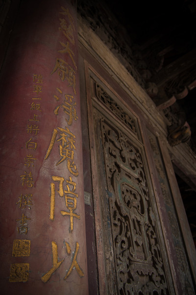 An engraved pillar and wall at the temple